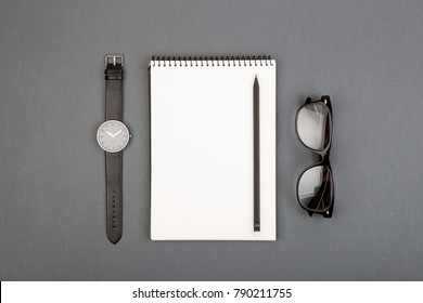 spiral blank notebook, pencil and glasses on gray background, top view