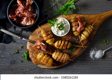 Spiral cut small potatoes on skewers baked with olive oil and served with  herb curd and fried bacon strips