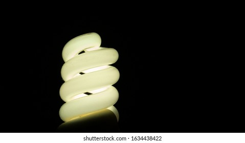 Spiral energy-saving lamp with warm light on a black background