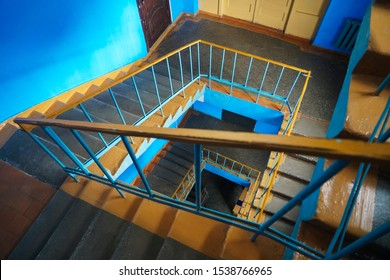 The spiral fire escape as orange staircase in squre style. A spiral staircase spiraling down about five floors. The winding concrete stairs are empty. The metal hand rail is nicely decorated.