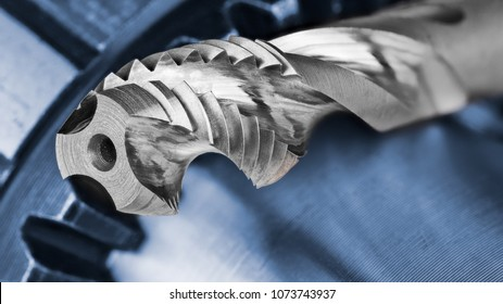 Spiral flute tap and chuck with blank copy space. Artistic close-up of the silver steel cutting tool for threading with the blue metallic cogwheel on background.