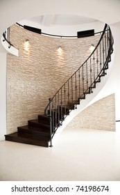 spiral hardwood floor staircase with tiled wall and metal railing