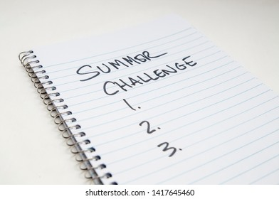 """A spiral lined notebook with """"Summer Challenge"""" and 1.2.3 written on it on a white background"""