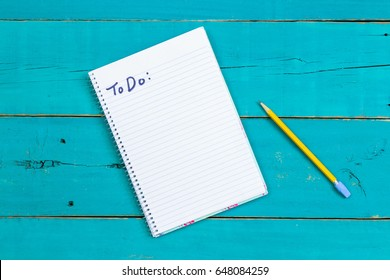 Spiral notebook with To Do: list and yellow pencil on rustic antique teal blue wood desk; above view looking down business background with white copy space