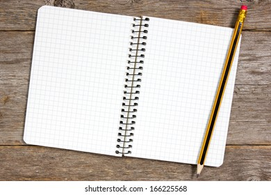 Spiral notebook and pencil on a wooden background