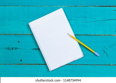 Spiral notebook with yellow pencil on rustic antique teal blue wood desk; above view looking down business background with white copy space