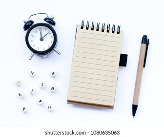 Spiral notepad with pencil as mockup for your design and cubes with letters. Note book on pastel white background, flat-lay style.