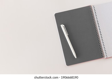 Spiral opened notebook with gray sheet and white pen. Layout and flat lay with place for text isolated on white background. Back to school. Top view, copy space. High resolution. Student workplace