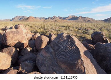 Spiral petroglyph attributed to the Hohokam people on Signal Hill with mountains and saguaros in the background in Saguaro National Park near Tucson, Arizona.