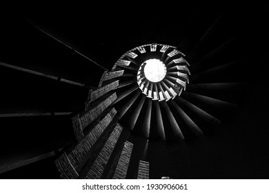 Spiral staircase with steps, upward view of a skylight, in monochrome