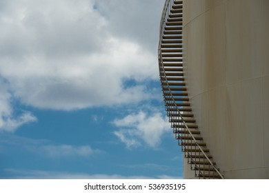 spiral stairs on a storage tank against a blue sky with white clouds