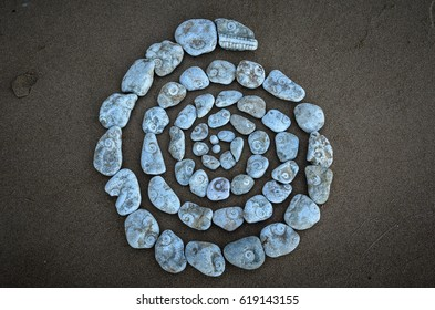 Spiral of textured pebbles on the sea beach