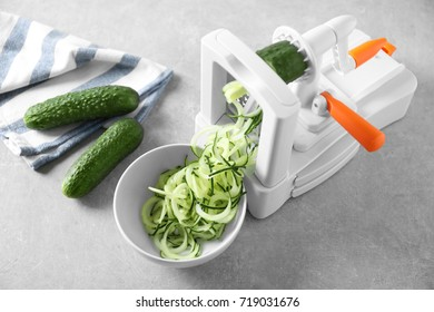 Spiral vegetable slicer with cucumber spaghetti on table
