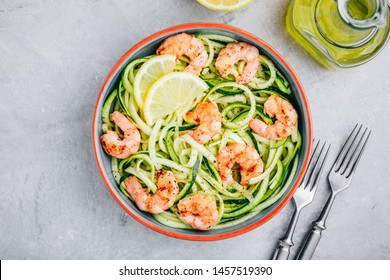 Spiralized zucchini noodles pasta with shrimps on gray stone background, top view
