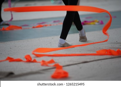 Spirals with orange art ribbon in fitness class. Young little gymnast girl in black sportswear dress, doing rhythmic gymnastics exercise with orange ribbon