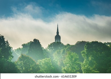 Spire of church above the trees in city Dresden.