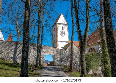 Spire of the der basilica St. Mang with city walls and  archway from viewpoint parkway tree garden from the city of fuessen during spring with blue sky