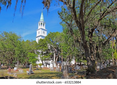 Spire main building and graveyard framed by Spanish moss-covered trees at the parish church of St. Helena in the historic district of downtown Beaufort, South Carolina
