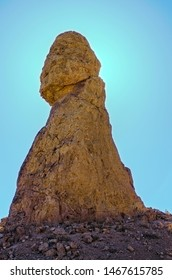 Spire on hilltop, fat at base and narrows going up to rounded top. Rock formation against a light blue sky.