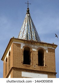 Spire tiled roof of the bell tower. Church in Guadix. Spain