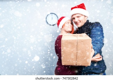 Spirit of Christmas and new year. Concept of a holiday and days off. A loving couple in Santa Claus hats. Guy hugging girl and holding gift in hand, focus on gift. with snowfall
