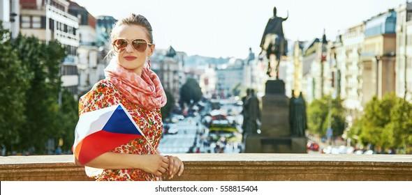 The spirit of old Europe in Prague. modern traveller woman on Vaclavske namesti in Prague, Czech Republic with Czech flag