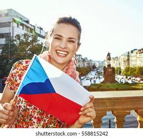 The spirit of old Europe in Prague. Portrait of smiling modern woman on Vaclavske namesti in Prague, Czech Republic showing flag