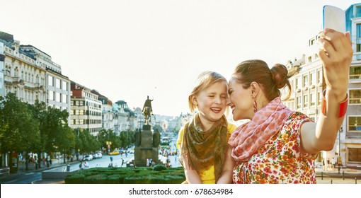 The spirit of old Europe in Prague. smiling young mother and child tourists on Vaclavske namesti in Prague, Czech Republic with phone taking selfie