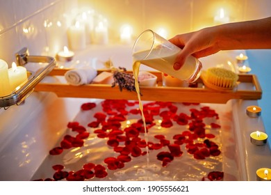 Spiritual aura cleansing flower bath for full moon ritual with coconut milk, candles, aroma salt, lavender and rose petals. Body care and mental health routine.
