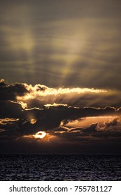 Spiritual awakening. Dramatic sunrise representing the creation of heaven and earth. Dawn over the ocean horizon. Picturesque aesthetic image of sun rising behind clouds at sea.