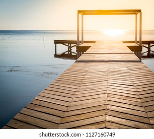 Spiritual background of sunrise at the end of a wooden boardwalk over calm water with copy space