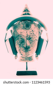 Spiritual music therapy. Contemporary image of Buddha head with modern headphones representing religious, new age, or trance music. Divine pink white light background for purity and enlightenment.