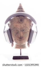 Spiritual music therapy. Religious or new age music as a calming lifestyle enhancement choice  represented by serene Buddha head with modern headphones against divine white enlightenment background.