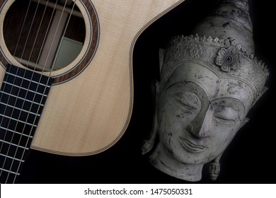 Spiritual music. Traditional meditating buddha statue with acoustic folk guitar. Representing music therapy, religious music and healing the mind. Chill-out new age music isolated on black background.