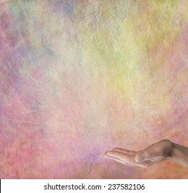 Spiritual Rainbow Message Board Background  -  Male hand outstretched with palm facing up on a multicolored stone effect  background with plenty of copy space