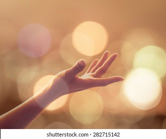 Spiritual support, charity, holy and world human spirit day concept with woman's hand reaching upward to heaven under candle moon light