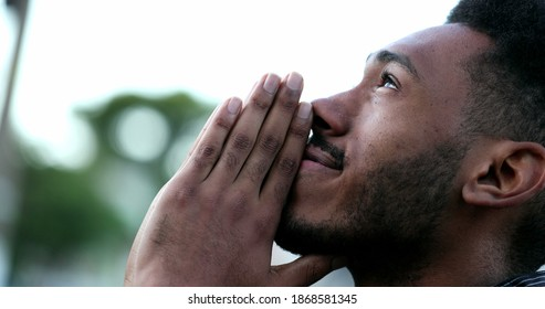 Spiritual young black African man praying to GOD. Person looking to sky with HOPE and FAITH