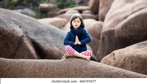 spiritual young kid with eyes closed trying to relax, pray and breathe alone for yoga outdoor, seeking for mindfulness, sitting on giant granite stones, springtime