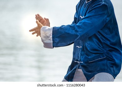 Spiritual Young man practicing traditional Tai Chi Chuan, Tai Ji and Qi gong in the park for healthy, traditional chinese martial arts concept.