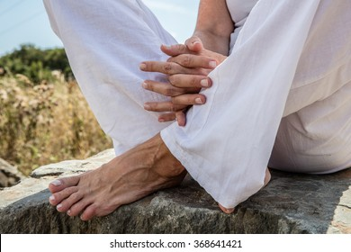 spirituality outdoors - closeup of praying hands and bare feet of a yoga woman sitting on a stone in lotus position, wearing white,low angle view