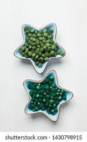 Spirulina algae and chlorella tablets on white marble