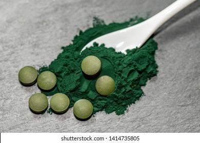 Spirulina Algae Powder and pills on black background .Macro, selective focus