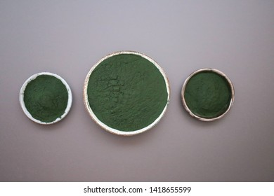 Spirulina algae.  powder in round cups set on a black table.organic spirulina algae powder.Super food concept.Spirulina bacterium - algae, nutritional supplement.