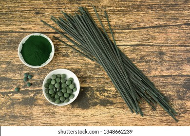 Spirulina algae powder, tablets and dried pasta on wooden background