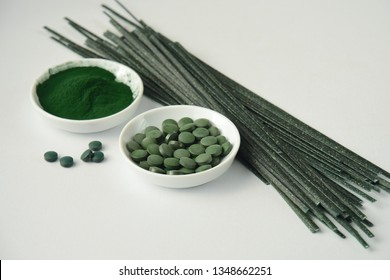 Spirulina algae powder, tablets and dried pasta on white background