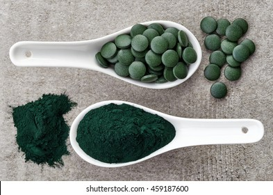 Spirulina algae powder and tablets on gray background from top view