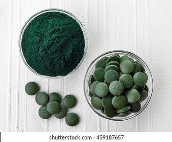 Spirulina algae powder and tablets on white wooden background from top view