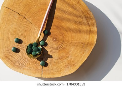 Spirulina or chlorella tablets in a spoon on natural wooden cut down. Healthy living concept.