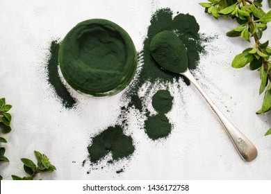 Spirulina green powder isolated with spoon on a textured background. Close up of spirulina powder, a healthy supplement to improve health. Spirulina algae adds vitamins and minerals to your diet.