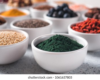 Spirulina powder in small white bowl and other superfoods on background. Selective focus. Different superfoods ingredients. Concept and illustration for superfood and detox food